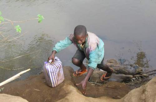 Boy collecting drinking water from muddy pool