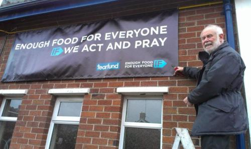 With a friend, putting the Enough Food for Everyome banner on the church wall