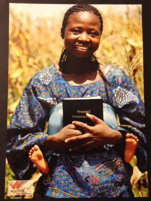 A lady from Burkina Faso holds the  New Testament in her Bissa Lebir language