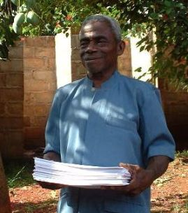 Bai Laurent holding the prinout of the Kouya New Testament at the final checking session