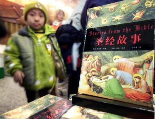 A young boy stands by a display featuring Bible stories translated into Chinese at the Xinhua bookstore in Beijing | Reuters