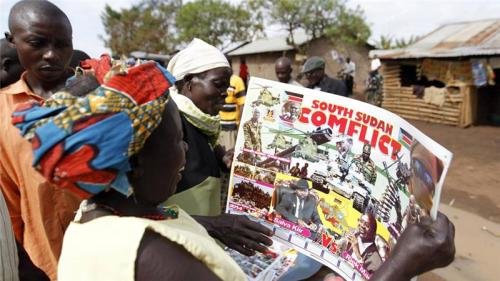 Refugees from South Sudan look at a photo montage depicting the conflict in their country on a calendar at the Kyangwali refugee settlement in Hoima district in Uganda
